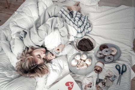 Photo pour Bonbons et photos. Femme solitaire stressée portant un pyjama couché au lit près de bonbons et de photos - image libre de droit