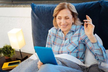 Photo pour Comprimé bleu comptable. Agréable femme aux cheveux bruns en riant tout en vérifiant son comprimé le matin - image libre de droit