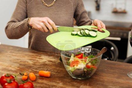 Photo pour Positif pendant la cuisson. Femme précise qui travaille dur en ajoutant des concombres hachés dans un bol en verre tout en finissant sa cuisson - image libre de droit