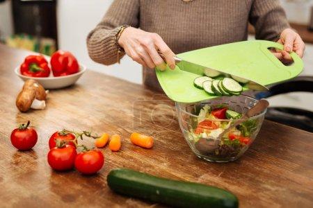 Photo pour Ajout de concombres hachés. Femme attentive dans beige pull jeter des légumes dans le bol en verre tout en ayant un dîner léger - image libre de droit