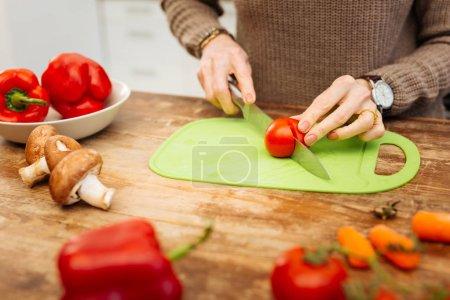 Photo pour Tomate de coupe. Femme soignée dans pull chaud prépare son dîner tout en hacher tomate sur les plus petites pièces - image libre de droit