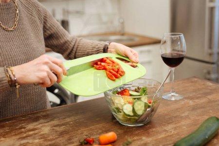 Photo pour Panneau de plastique vert. Dame précise en pull beige, ajouter les tomates hachées dans bol en verre pour salade fini - image libre de droit
