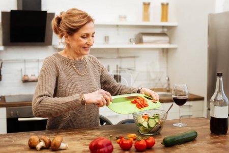 Photo pour Ajouter les tomates hachées. Rayonnant de lumière aux cheveux femme séjournant dans la cuisine et préparer un repas léger tout en ayant le vin à proximité - image libre de droit