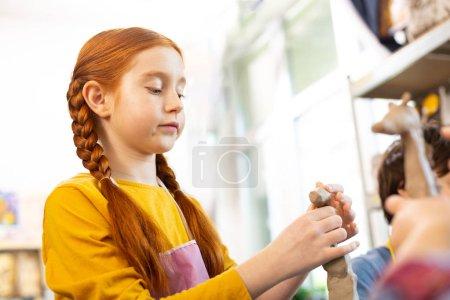 Foto de Chica involucrada. Pelirroja atractiva chica creativa sintiéndose involucrado en el modelado de animales de arcilla - Imagen libre de derechos