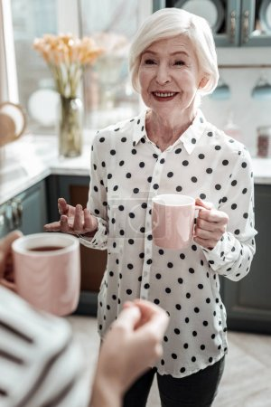 Photo for Feeling good. Cheerful beautiful aged woman looking stylish and glad while standing with a cup of tea and having a pleasant conversation - Royalty Free Image
