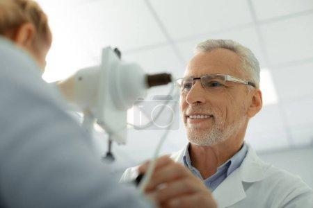 Photo pour Médecin des yeux souriant. ophtalmologiste barbu aux cheveux gris portant des lunettes et uniforme blanc souriant - image libre de droit