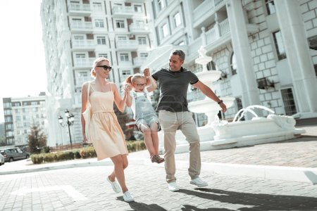 Photo pour Du temps en famille. mari et femme joyeux soulevant leur petite fille tenant ses mains marchant dans la rue de la ville . - image libre de droit