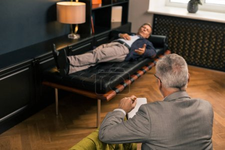 Photo pour Écouter un patient. Portrait d'un psychologue professionnel assis dans un fauteuil tout en écoutant un patient allongé sur le canapé - image libre de droit