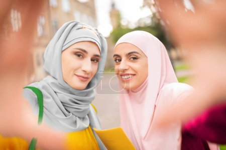 Muslim women wearing hijabs smiling while making selfie
