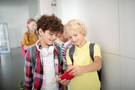Photo pour Jeu vidéo préféré. Blonde garçon aux cheveux montrant son jeu vidéo préféré à meilleur ami tout en ayant pause - image libre de droit