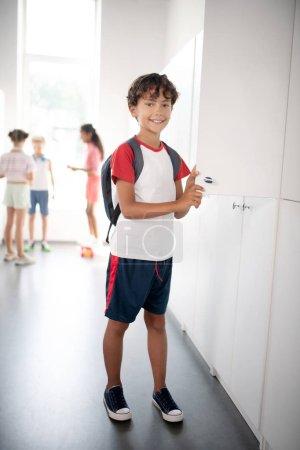 Dark-haired boy wearing sport clothing standing near locker