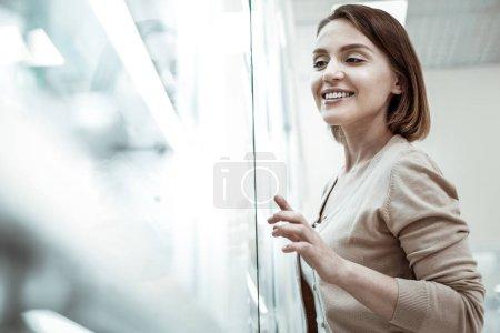 Photo pour Indication du médicament. Une dame pointilleuse avec un large sourire sincère indiquant le médicament requis dans la fenêtre de la pharmacie . - image libre de droit