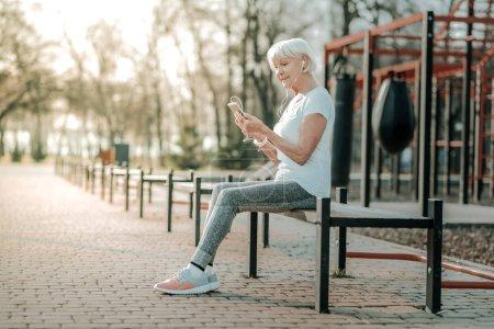 Photo pour Je porte des écouteurs. Une femme âgée joyeuse se détendant sur le banc près du terrain de sport, portant des écouteurs et regardant son téléphone avec intérêt . - image libre de droit