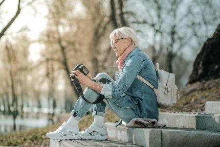 Photo pour Dame aînée avec caméra. Senior dame à la mode dans des lunettes et sac à dos blanc à la mode assis sur les marches du parc avec caméra - image libre de droit