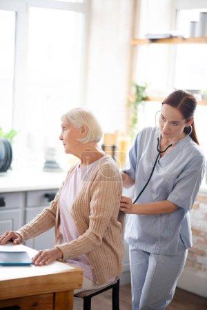 Photo pour Elle examine une retraitée. Infirmière portant l'uniforme examinant dame à la retraite se sentant malade et fatigué - image libre de droit