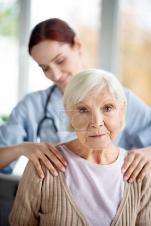 Photo for Massage for woman. Professional pleasant caregiver doing massage for retired aged woman - Royalty Free Image