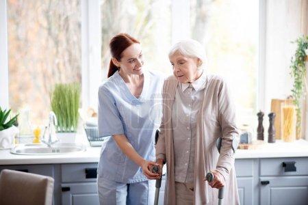Photo pour Aide soignante. Aidante aux cheveux roux souriante aidant la femme âgée à faire des pas - image libre de droit
