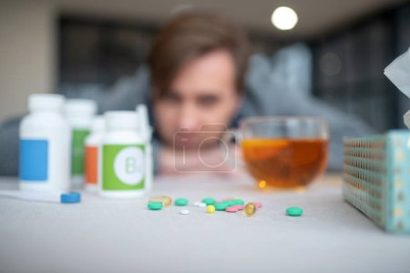 Photo for Pills near tea. Close up of pills lying on the table near cup of tea for sick man - Royalty Free Image
