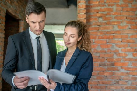 Photo pour Contrat. Homme investisseur en costume noir lisant le contrat - image libre de droit