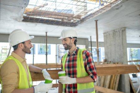 Photo pour Site de construction. Travailleurs du bâtiment en gilets jaunes et gants ayant une pause café - image libre de droit