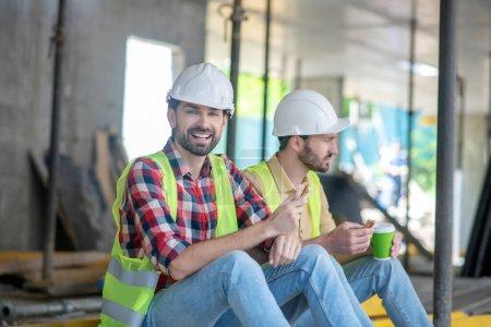Photo pour Site de construction. Travailleurs du bâtiment en gilets jaunes et casques assis, prendre un café avec des sandwichs, rire - image libre de droit