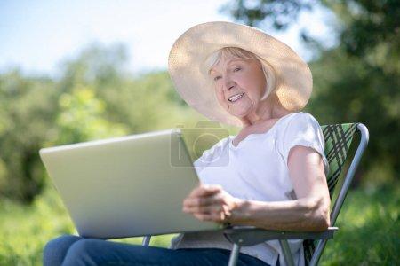 Photo pour Connexion sans fil. Une femme âgée travaillant avec l'ordinateur en plein air - image libre de droit