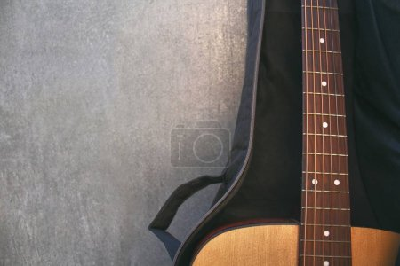 Cropped shot of guitar with case by concrete wall...