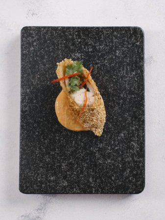 Gourmet snack with wrapped fish, sesame seeds and tropical sauce served on black stone plate