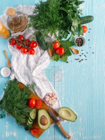 Ingredients for cream of avocado soup on blue wooden background