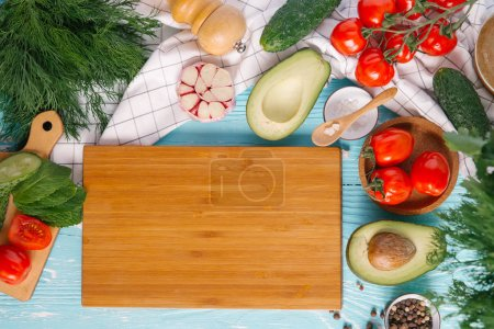 Photo for Ingredients for cream of avocado soup around wooden chopping board on blue wooden background - Royalty Free Image