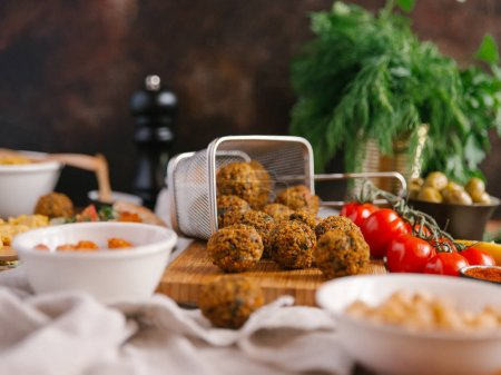 Photo for Fresh fried falafel balls on wooden board surrounded with different ingredients - Royalty Free Image