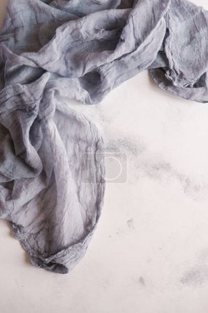 Top view of grey linen cloth on white concrete background