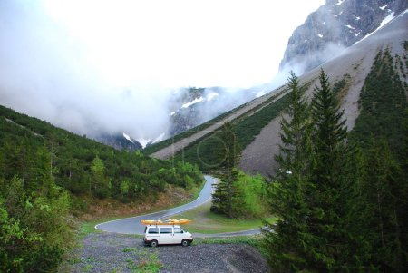White van with two kayaks standing on roadside verge in mountains