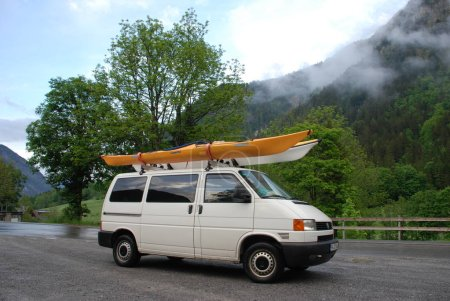 White van with two kayaks on roof on mountain road