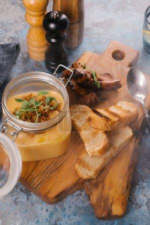 Photo pour Soupe CREME en pot de verre servi avec toasts et nervures sur planche à découper en bois - image libre de droit