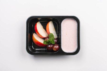 Photo pour Vue de dessus d'une bonne nutrition de fruits et d'yogourt en boîte sur fond blanc - image libre de droit