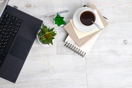 Photo pour Bureau table en bois de bureau de lieu de travail d'affaires, ordinateur portable, plante artificielle et tasse à café avec espace de copie. Vue du dessus - image libre de droit