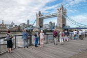 LONDON / UNITED KINGDOM - JUNE 11, 2017: Tourists in the city center by the Tower Bridge over Thames River