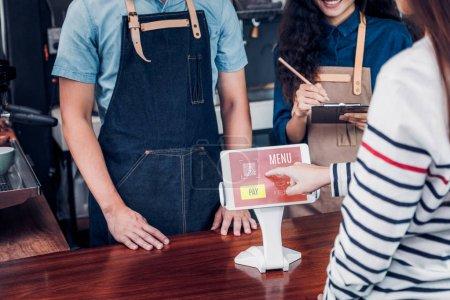 Photo pour Client self service commander un menu de boissons avec écran de tablette au comptoir bar café, vendeur café accepter le paiement par mobile.digital concept de style de vie - image libre de droit