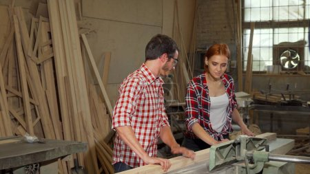 Two young carpenters doing woodwork at furniture manufacturing