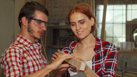 Male carpenter helping his female assistant at the workshop