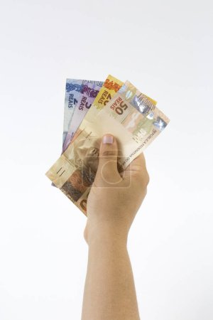 Person holding some money of Brazil