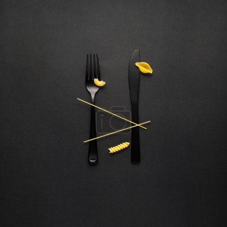 Creative still life photo of fork and spoon with raw pasta on black background.