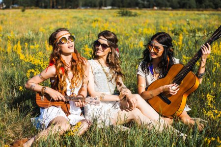 Three young hippie girls sitting on plaid with guitars outdoors