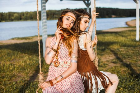Two hippie girls with feathers in long hair sitting on swing outdoors