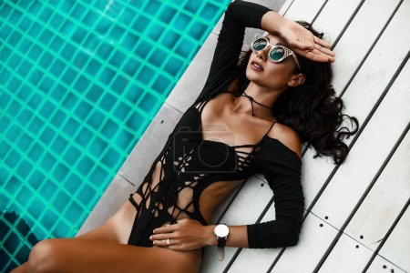 beautiful amazing young girl, lie on a wooden white surface, dressed in black and white swimsuits, fashion accessories, sunglasses, tanned ideal bodies, leather, chic hair, makeup