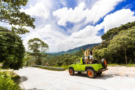 two girls best friends travel on a tropical island in a car with an open top are having fun having a smile. enjoyment travel, excursion summer dressed shorts T-shirts sunglasses, blue sky
