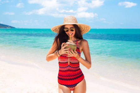 Photo for Beautiful girl in a swimsuit with ethnic prints, a straw hat holding a fresh coconut in the sand against the blue sea and the beach smiling. Summer vacation, travel, pleasure, joy - Royalty Free Image