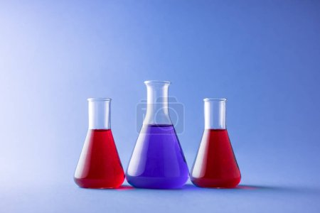 Three erlenmeyer flasks over colorful background
