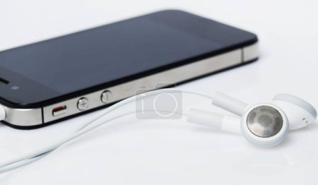 Photo for Technology. Smartphone with headphones on a white background - Royalty Free Image